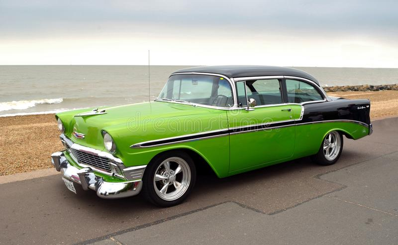 Classic Green and Black Chevrolet Belair American Automobile parked on seafront promenade. stock image