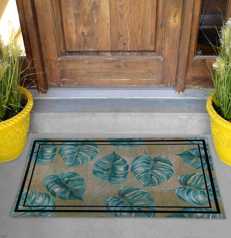 Classic green leaves Outdoor Door mat with twin black borders outside home with yellow flower pots stock photos