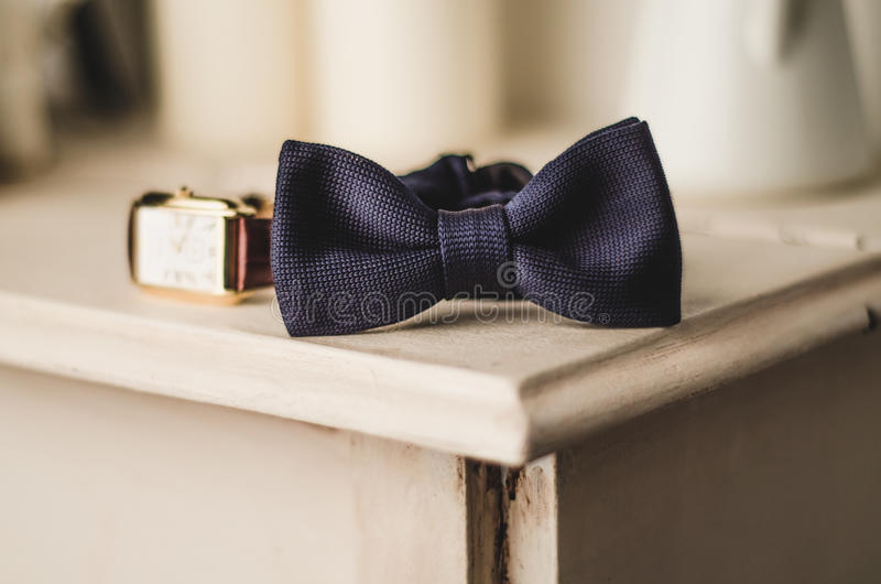 Classic groom accessories: blue bow tie and watch on a wooden table. Set of men's stylish vintage clothing. Male royalty free stock photo