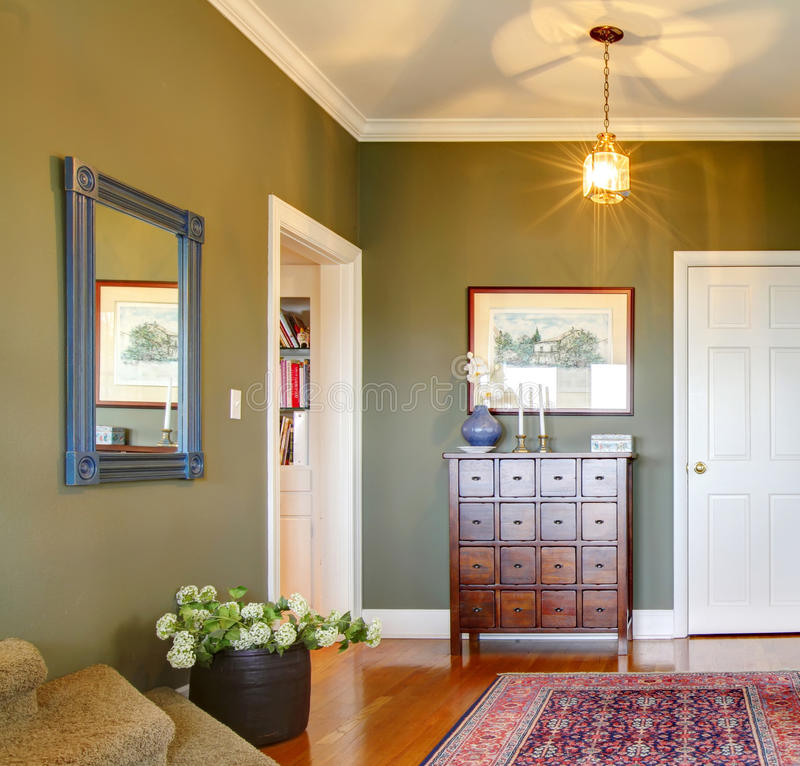 Classic Hallway with green walls, flowers and rug. stock images