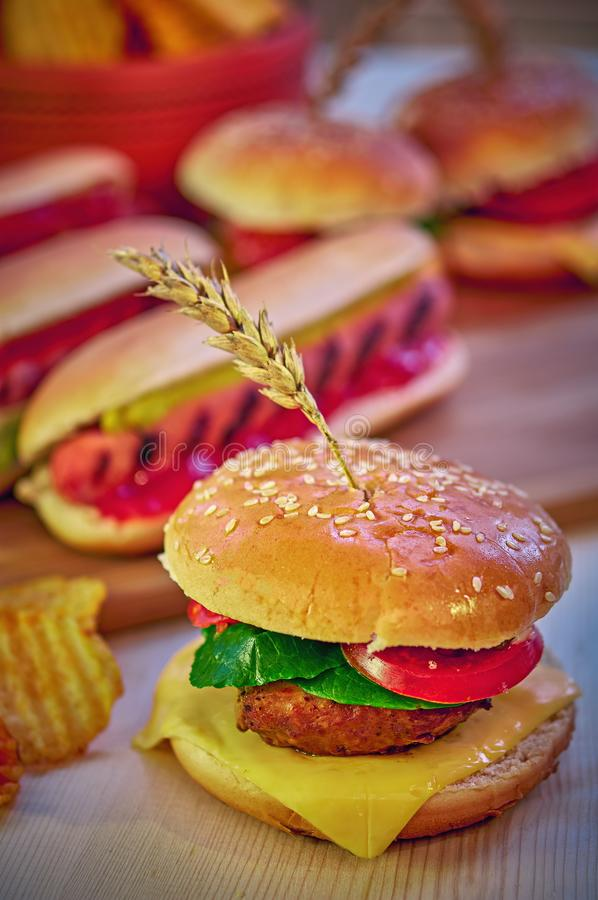 Classic Hamburger american meal. Homemade grilled and glazed beef burger with lettuce, cheese and tomato on wooden table. stock photos