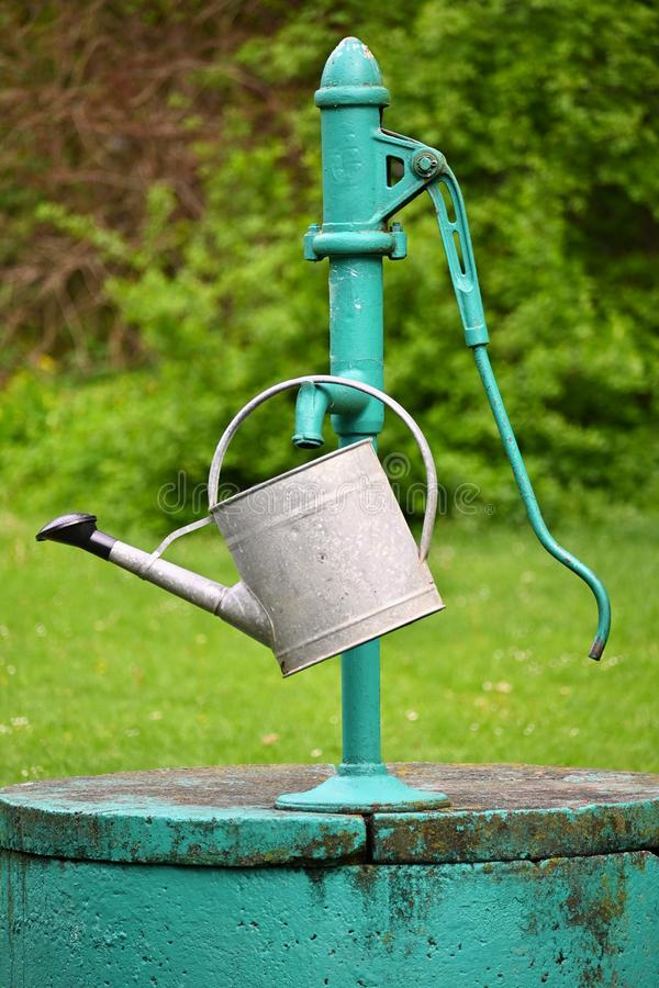 Classic hand pump for water - well with kettle for watering the garden stock photos