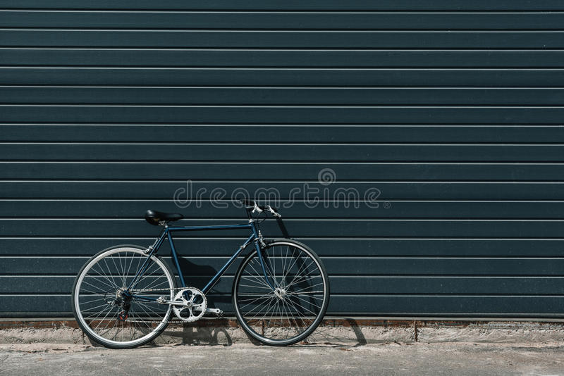 Classic hipster bicycle standing near black wall outdoors royalty free stock photo