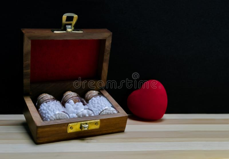 Classic Homeopathy for Heart – Close view of homeopathy medicine bottles in wooden old box with red heart on wood and dark royalty free stock photography
