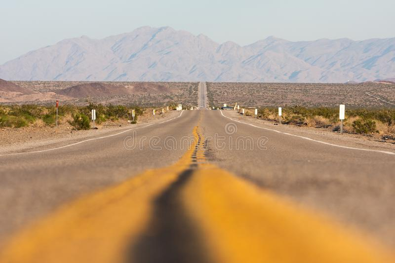 Classic horizontal panorama view of an endless straight road running through the barren scenery of the American stock photography