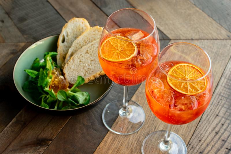 Classic Italian aperitif `aperol stpritz` with ice and with appetizers royalty free stock photo