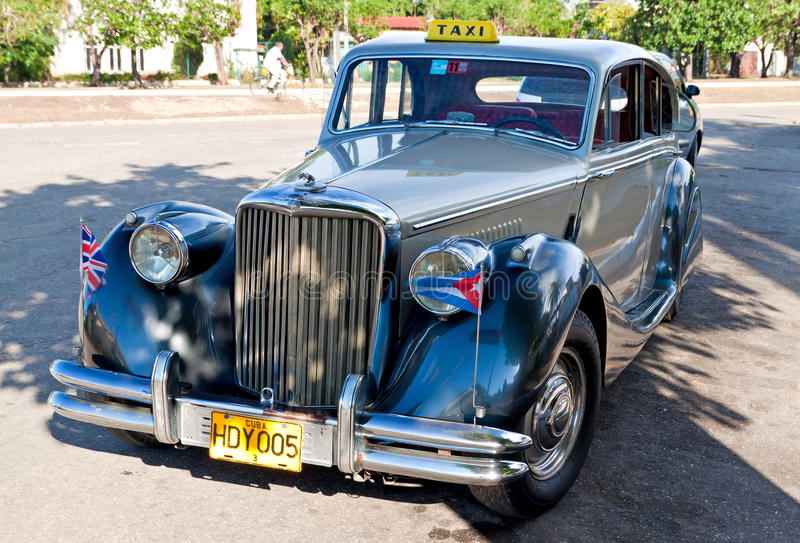 Classic Vintage Jaguar Car In Havana With The Cuban And British Flags