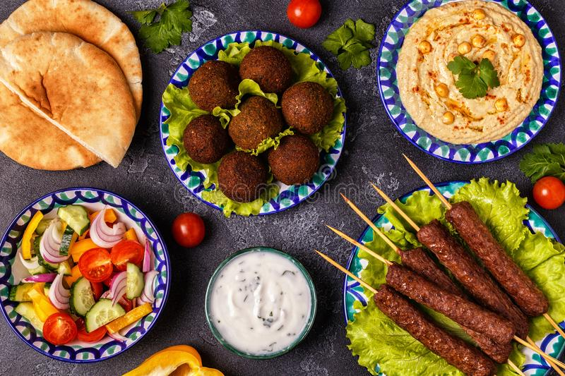 Classic kebabs, falafel and hummus on the plates. royalty free stock images