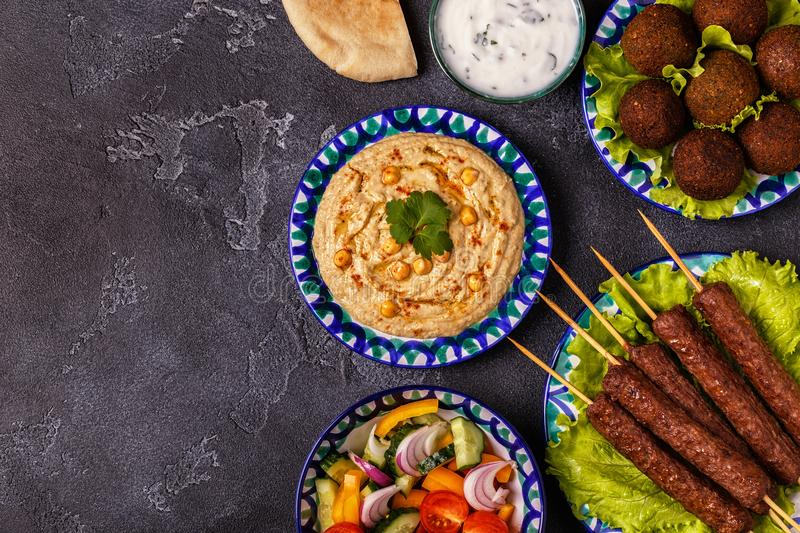 Classic kebabs, falafel and hummus on the plates. royalty free stock photo