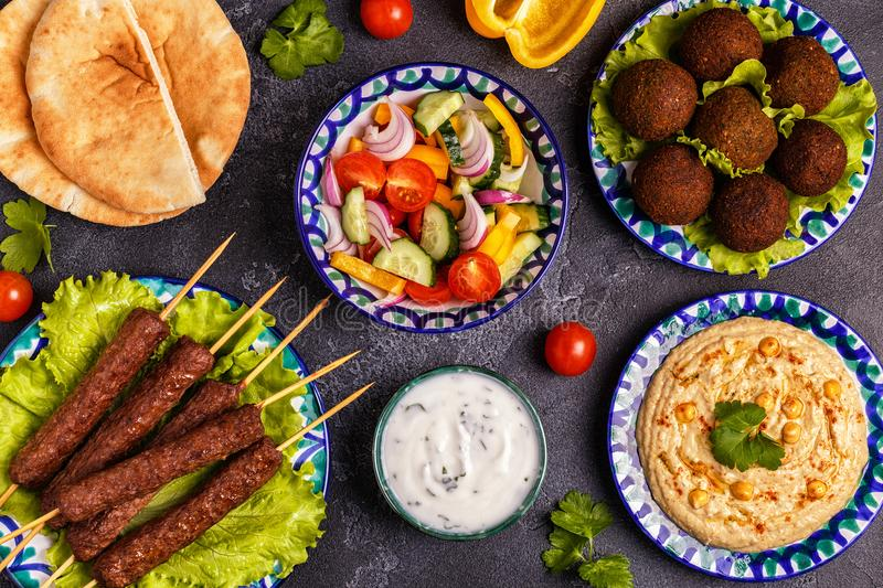 Classic kebabs, falafel and hummus on the plates. stock image