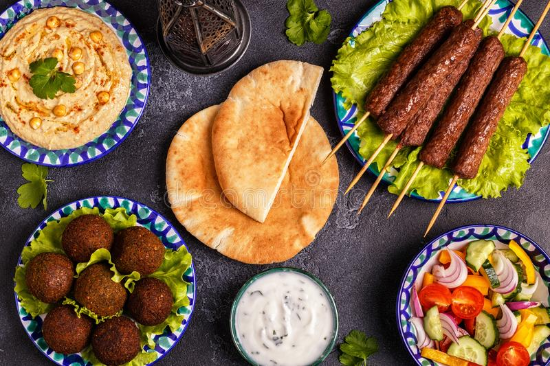 Classic kebabs, falafel and hummus on the plates. stock photos