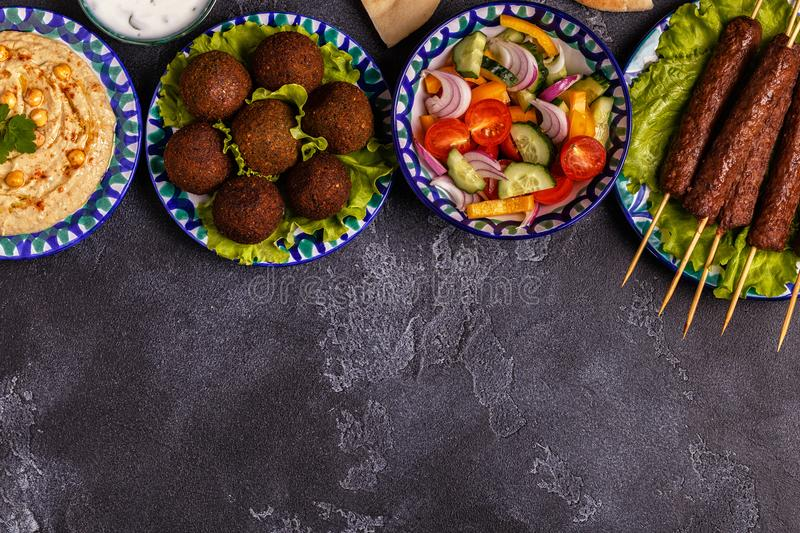 Classic kebabs, falafel and hummus on the plates. stock images