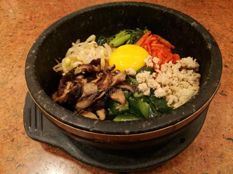 Classic Korea food vegetable Bibimbap hot stone pot,rice carrot,spinach,mushroom,cucumber,seaweed,raw yolk egg and hot spicy chili stock photos