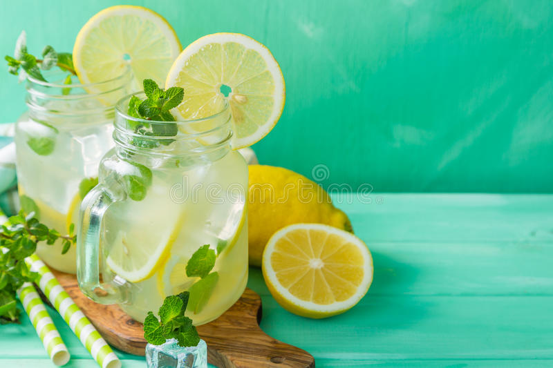 Classic lemonade in glass jars. Wood background royalty free stock photography