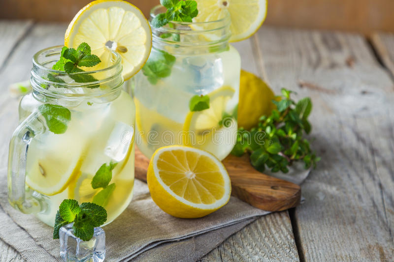 Classic lemonade in glass jars. Wood background royalty free stock photo