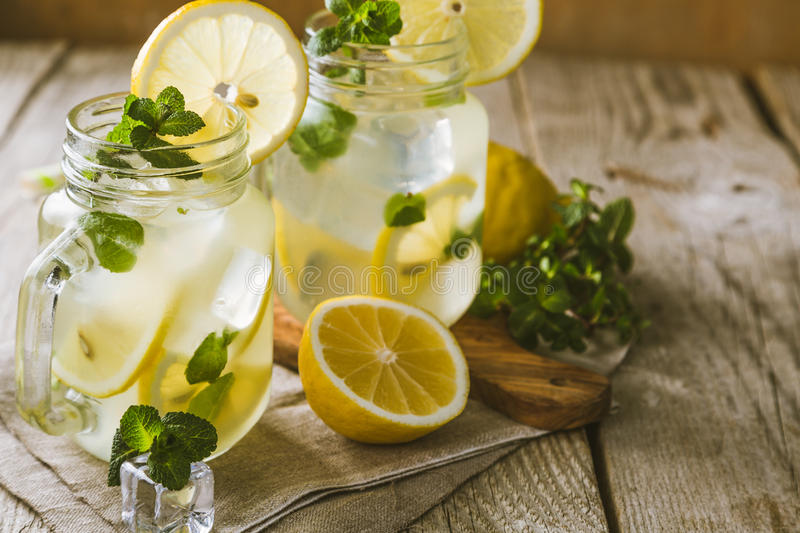Classic lemonade in glass jars. Wood background stock photography