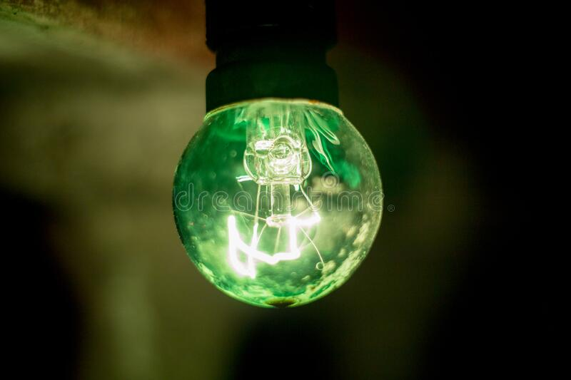 Green closeup of a retro 5W watt bulb with glowing filament in a natural background. Side view, close up, soft focus, selective focus stock photo