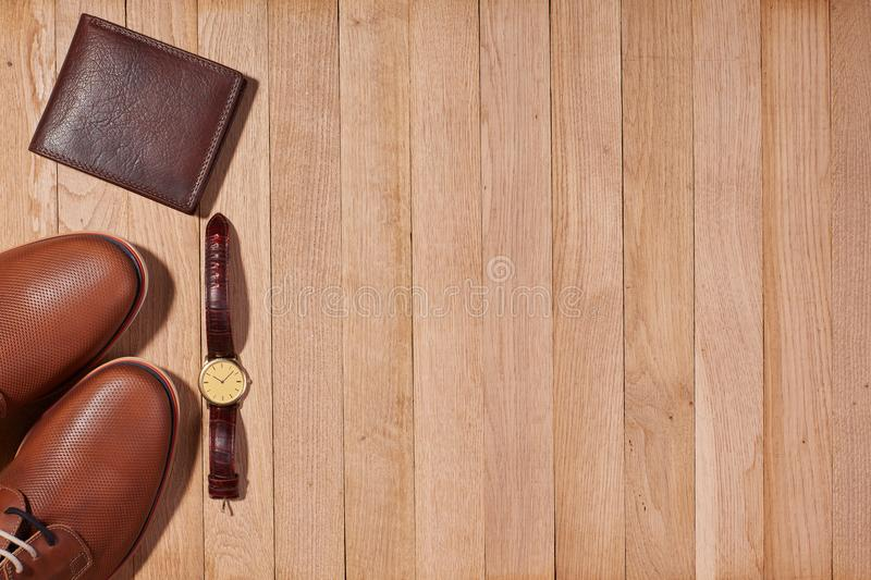 Classic male shoes, wallet and watch. Still life with classic brown leather shoes for men , wallet and watch lies on a wooden background with copy space. Top royalty free stock photo
