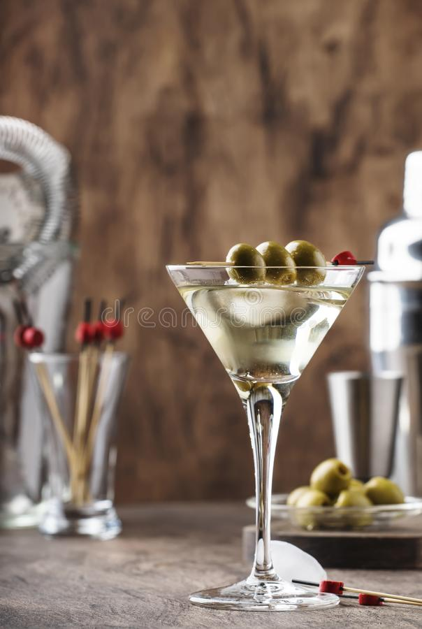 Classic Martini vodka cocktail, with dry vermouth, vodka and green olives, bar tools, vintage wood bar counter, selective focus stock images