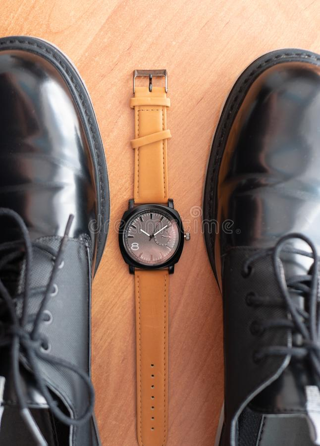 Classic mechanical wrist watch lay between pair of man black formal shoes. top view royalty free stock image