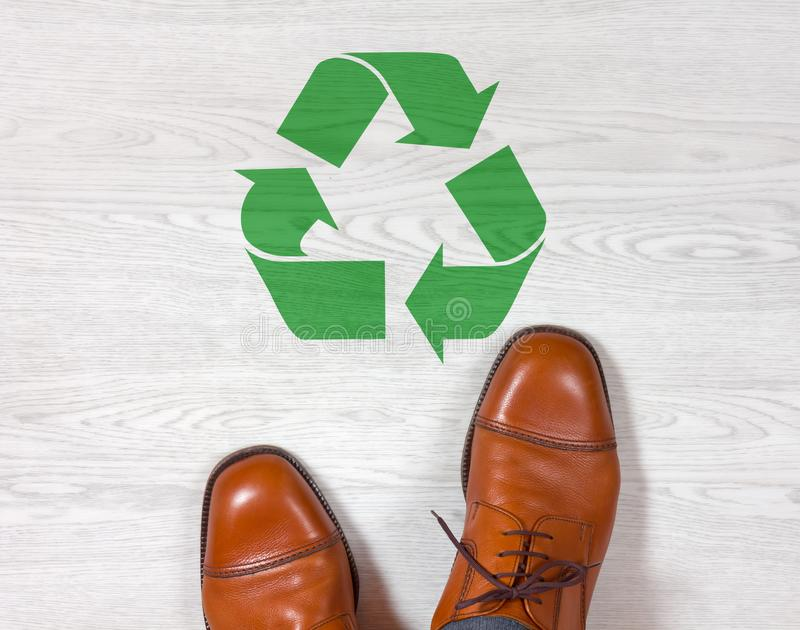 Classic mens shoes with a recycling symbol on the floor stock photo