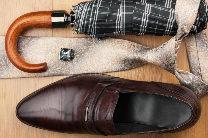 Classic mens shoes, tie, umbrella,cufflinks on the wooden floor royalty free stock image