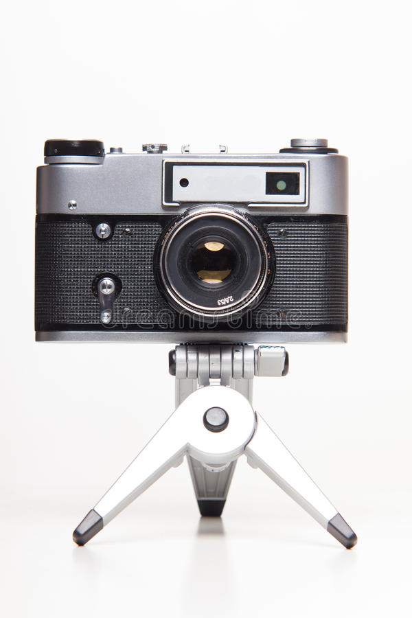 Classic 35mm old analog camera on tripod. Studio shoot royalty free stock photography