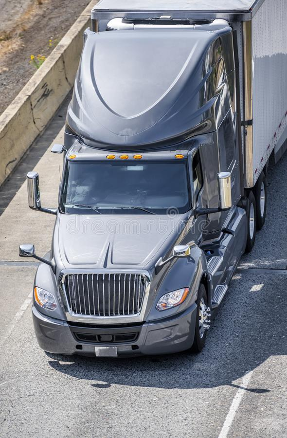 Classic modern gray big rig semi truck transporting frozen products in refrigerator semi trailer moving ahead on the multiline stock photo