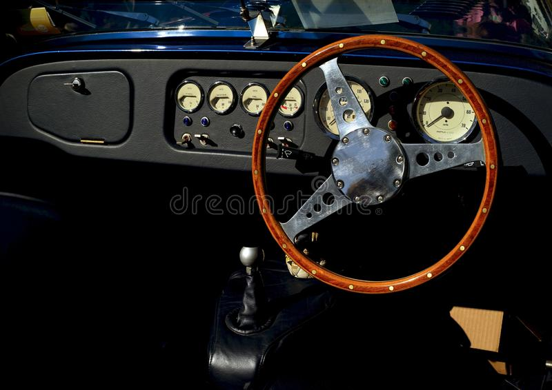 Classic Morgan automobile interior. The sleek dashboard and wooden steering wheel of a classic Morgan car is shown along with the manual transmission stick shift royalty free stock photography