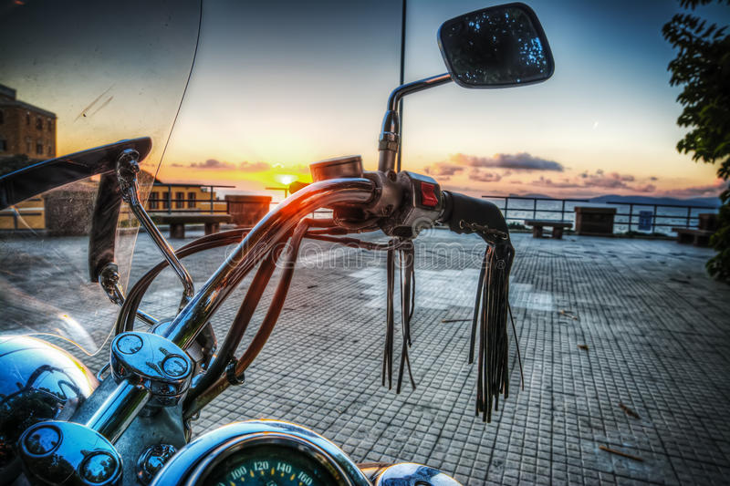 Classic motorcycle by the sea at sunset. In hdr tone mapping effect royalty free stock images