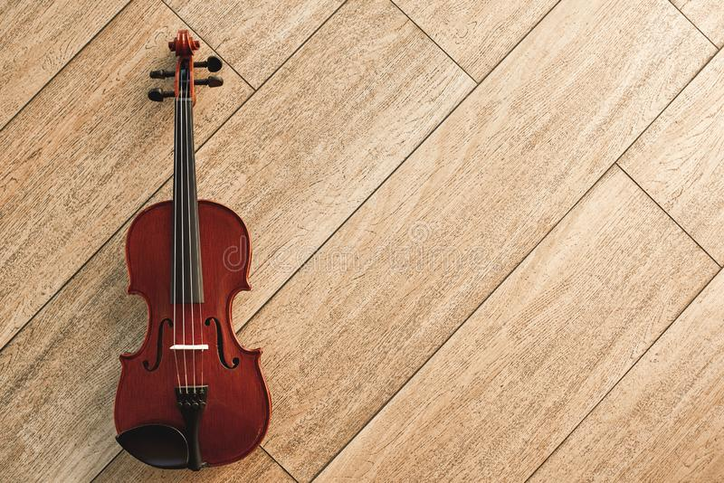 Classic musical instrument. Top view of the brown violin on the wooden floor royalty free stock photo