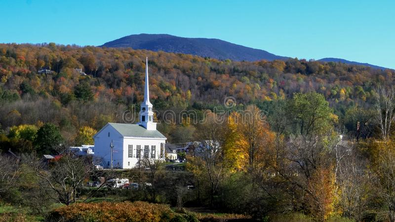 Classic new england white church at stowe and hill with fall foliage stock photo