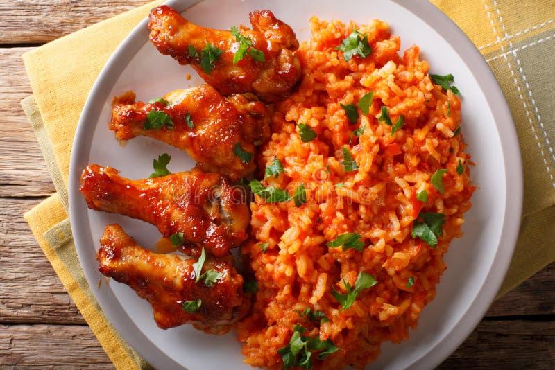Classic Nigerian Jollof�Rice with fried chicken wings close-up. Classic Nigerian Jollof�Rice with fried chicken wings close-up on a plate. horizontal royalty free stock image