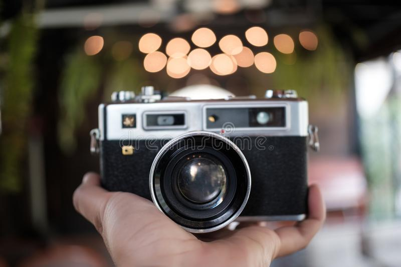 Classic old analog camera vintage color effect camera in hand. Concept royalty free stock photos