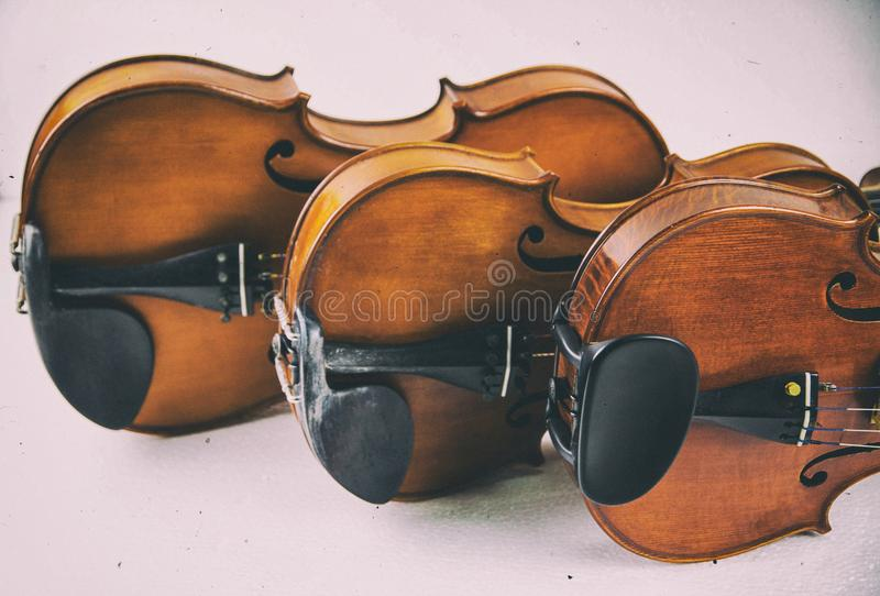The classic old film design background of wooden violin,three violins stacked on board,warm light tone,grainy film design royalty free stock photos
