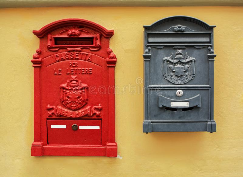 Classic old red and black Italian postboxes on a yellow painted stucco wall. Florence, Italy royalty free stock photos