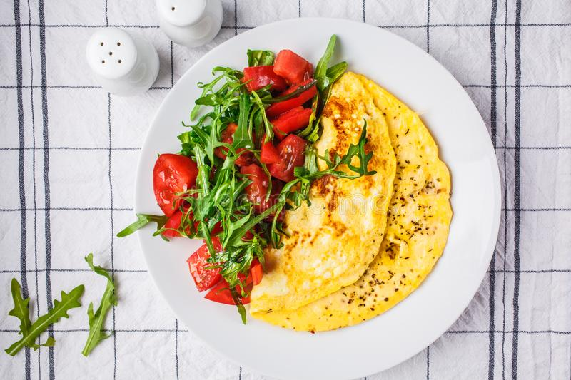 Classic omelet with cheese and tomatoes salad on white plate, top view stock images