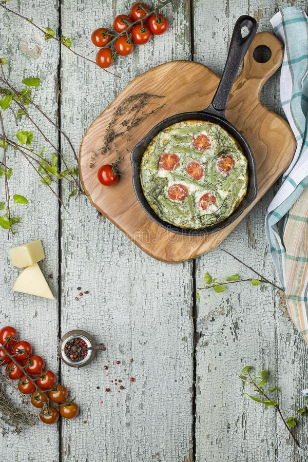 Classic omelet with cherry tomatoes, cheese and herbs royalty free stock image