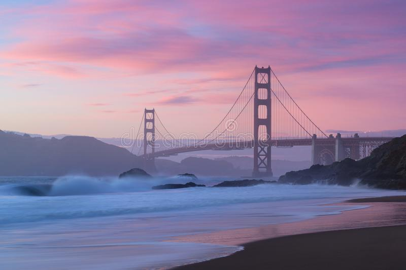 Classic panoramic view of famous Golden Gate Bridge seen from scenic Baker Beach in beautiful golden evening light on a dusk. Classic panoramic view of famous royalty free stock images