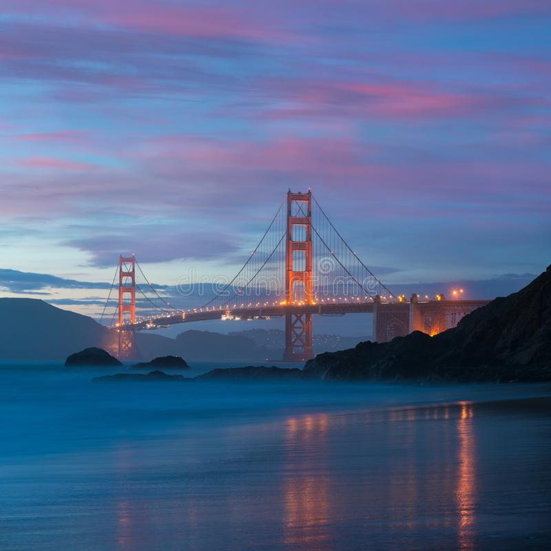 Classic panoramic view of famous Golden Gate Bridge seen from scenic Baker Beach in beautiful golden evening light on a dusk. Classic panoramic view of famous stock photography