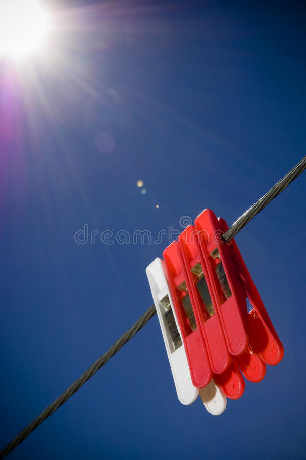 Classic Pegs in Sun. Generic pegs on a washing line in clear blue sky royalty free stock photo