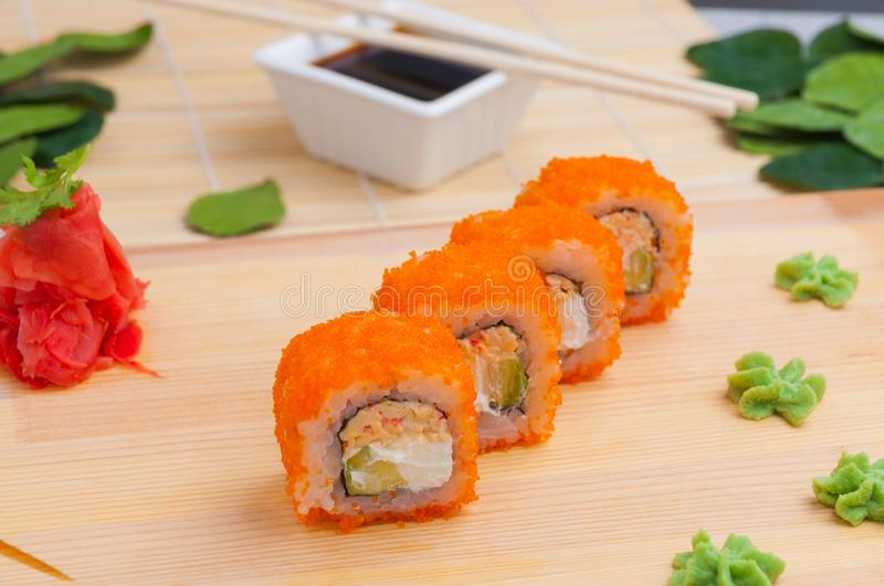 A classic Philadelphia roll with wasabi, ginger and soy sauce on a wooden Board. Salmon, Philadelphia cheese, cucumber royalty free stock photography
