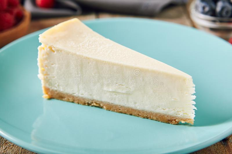 Classic Plain New York Cheesecake on Blue Plate. Close Up. Triangular Slice of Tasty Homemade Cheese Cake on Blurred Wooden Rustic Vintage Background with stock image