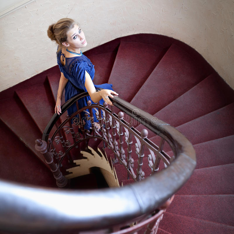 Classic portrait of elegant woman on staircase. Portrait of elegant woman on circular staircase stock image