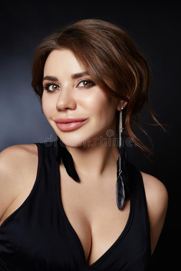 Classic portrait of a woman in a black dress on a dark background close-up. Smooth clean skin of the face girl. Large woman eyes royalty free stock photo