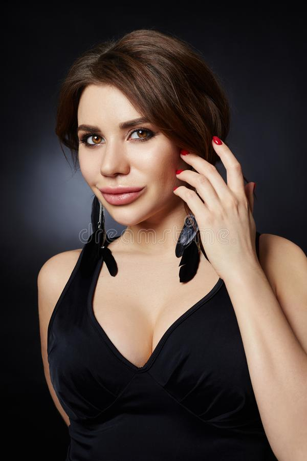 Classic portrait of a woman in a black dress on a dark background close-up. Smooth clean skin of the face girl. Large woman eyes stock image