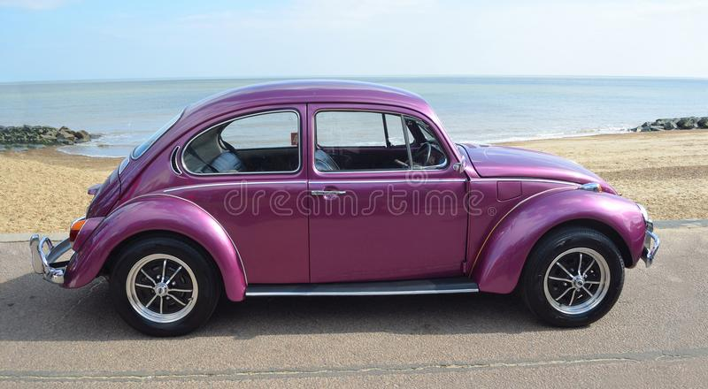 Classic Purple Volkswagen Beetle Motor Car Parked on Seafront Promenade. royalty free stock photo
