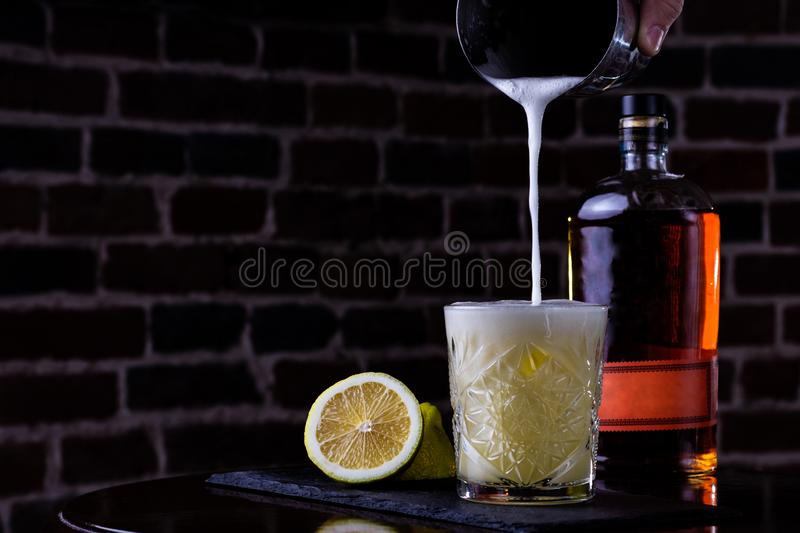 A classic recipe for whiskey sour - with bourbon, cane syrup and lemon juice, garnished with orange. Traditional aperitif. Space stock photography