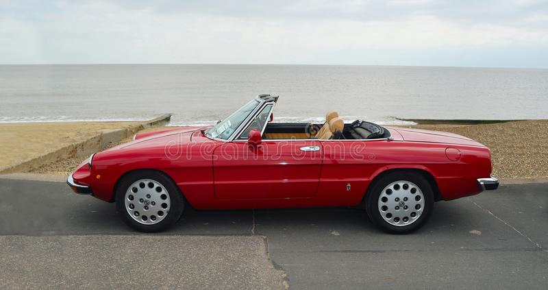 Classic Red Alpha Romeo Convertible Motor Car Parked on Seafront Promenade. stock photo