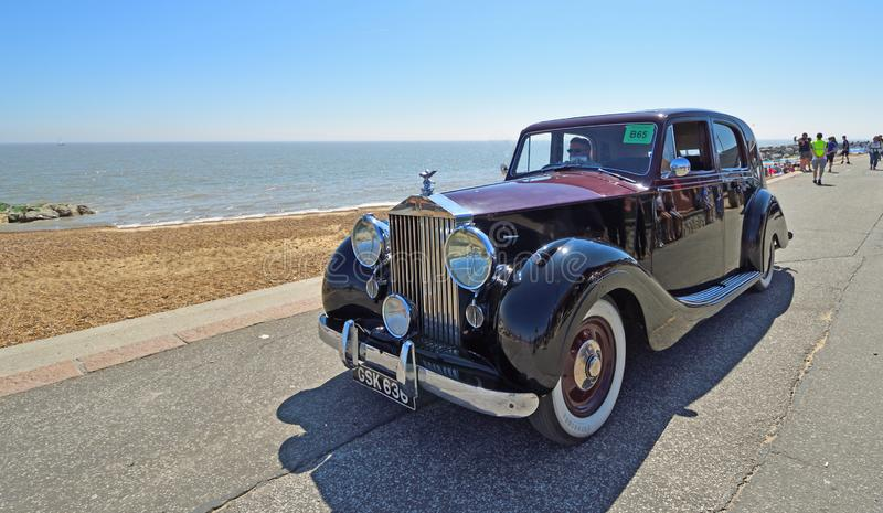 Classic Red & Black Rolls Royce Motor Car being driven along Seafront Promenade. FELIXSTOWE, SUFFOLK, ENGLAND - MAY 06, 2018: Classic Red & Black Rolls Royce stock images